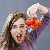 Surprised girl questioning strangely red and fresh tomatoes about pesticides Royalty Free Stock Images