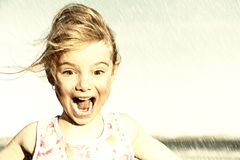 Surprised girl in rain. A little girl squeals with delight in the sudden rain. Sepia treatment Royalty Free Stock Photography