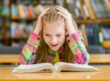 Surprised girl reading a book in the library Royalty Free Stock Images