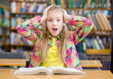 Surprised girl reading a book in the library Royalty Free Stock Photo