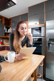Surprised girl reading her fun messages on tablet, eating cookie Royalty Free Stock Image