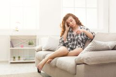 Surprised girl reading the results of her pregnancy test. Surprised redhead girl checking her recent pregnancy test, sitting on beige couch at home. Maternity royalty free stock images