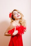 Surprised girl in red dress with flower barrette Royalty Free Stock Photos