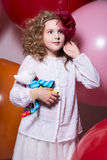 Surprised girl in a red hat in a white dress with a soft toy in stock images
