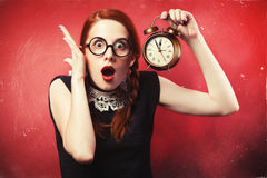 Surprised girl. Surprised redhead girl with clock Royalty Free Stock Photography