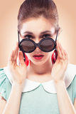 Surprised girl in round sunglasses. Beautiful young woman with glamour red lips make-up wearing round  black plastic-rimmed sunglasses and fancy plastic earrings Stock Photography