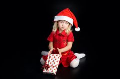 Surprised girl in santa cap with gift Stock Photo