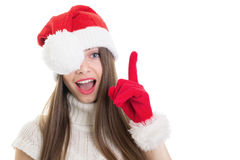 Surprised girl with Santa Claus beanie and gloves pointing up Stock Photography
