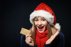 Surprised girl in Santa hat with blank credit card Stock Photo