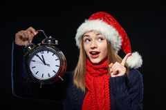 Surprised girl in Santa hat with clock. Closeup portrait of surprised girl wearing Santa hat holding big alarm clock time approaching midnight and pointing up at Royalty Free Stock Photography