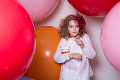 Surprised girl with a soft toy surrounded by huge balloons Royalty Free Stock Image