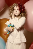 Surprised girl with a soft toy surrounded by huge balloons Royalty Free Stock Images