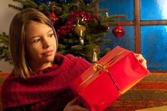 Surprised girl  studying christmas gift Stock Photography