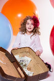 Surprised girl with a suitcase, in which lie the dollar amid lar Stock Images