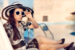 Surprised  Girl With Sunglasses and Hat Sitting on Sun Chair Royalty Free Stock Images
