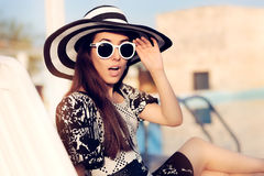 Surprised  Girl With Sunglasses and Hat Sitting on Sun Chair Stock Photo