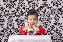 Surprised girl at table. Portrait of a surprised girl sitting at a table behind a Christmas mug Royalty Free Stock Photography