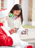 Surprised Girl Taking Gift From Santa Claus Royalty Free Stock Photos
