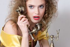 Surprised girl talking by vintage phone Royalty Free Stock Image