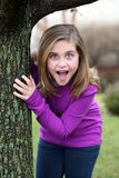 Surprised girl by tree Stock Photos