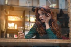 Surprised girl using mobile phone in cafeteria. Portrait of shocked young woman looking at smartphone. Her mouth is open with surprise. Lady is sitting at table royalty free stock photography