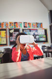 Surprised girl using virtual reality glasses in classroom Royalty Free Stock Images