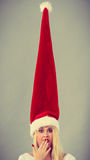Surprised girl wearing blowing santa claus hat Royalty Free Stock Image
