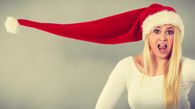 Surprised girl wearing blowing santa claus hat Stock Images