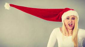 Surprised girl wearing blowing santa claus hat Royalty Free Stock Images
