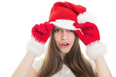 Surprised girl wearing Santa hat. Surprised cute happy teenage Caucasian brunette girl with Santa hat and gloves isolated on white background. Christmas concept Stock Photo