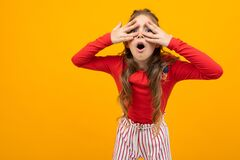 Free Surprised Girl With Curly Hair In A Red Blouse And Striped Trousers Peers Through The Palms On An Orange Background With Royalty Free Stock Photo - 173246585