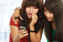 Surprised girls reading gossip Stock Photo