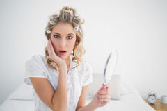 Surprised gorgeous blonde wearing hair curlers posing Stock Photo