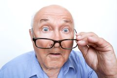 Surprised grandfather holding glasses Royalty Free Stock Image