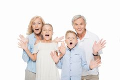 Surprised grandparents with grandchildren. Looking at camera isolated on white stock photos