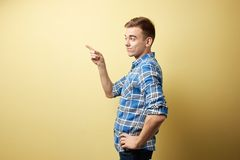 Surprised guy dressed in a plaid shirt and jeans stands next to yellow wall in the studio stock images