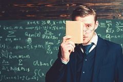 Surprised guy hiding his face behind book cover. Portrait of young scholar isolated on blurred green background royalty free stock photography