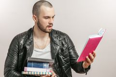 Surprised guy is reading a personal diary of his girlfriend. While sorting home library. close up side view shot. isolated white background. studio shot royalty free stock images