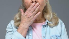 Surprised ha invecchiato a mano la bocca femminile della copertura, notizie scioccanti, difficoltà testimonia stock footage
