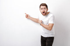 Surprised handsome man with beard pointing copy space. young man Stock Photo