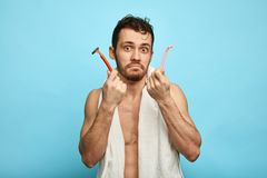Surprised handsome naked man with razors looking at the camera royalty free stock photo
