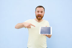 Surprised Handsome young man with a beard showing something on a tablet  on a blue background, bright and light Royalty Free Stock Images