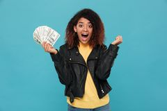 Surprised happy african woman in leather jacket holding money. And rejoice while looking at the camera over blue background Stock Image