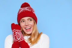 Surprised happy beautiful woman looking sideways in excitement. Christmas girl wearing knitted warm hat and mittens,  on b Stock Image