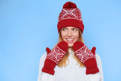 Surprised happy beautiful woman looking sideways in excitement. Christmas girl wearing knitted warm hat and mittens,  on b Royalty Free Stock Photography
