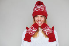 Surprised happy beautiful woman looking sideways in excitement. Christmas girl wearing knitted warm hat and mittens, isolated on g Royalty Free Stock Image