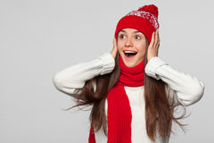 Surprised happy beautiful woman looking sideways in excitement. Christmas girl wearing knitted warm hat and scarf, isolated on gra Royalty Free Stock Images