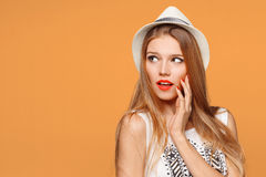 Surprised happy beautiful woman looking sideways in excitement. Isolated on orange background.  royalty free stock photo