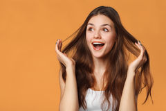 Surprised happy beautiful woman looking sideways in excitement. Isolated on orange background Royalty Free Stock Photography
