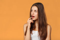 Surprised happy beautiful woman looking sideways in excitement.  on orange background Royalty Free Stock Images